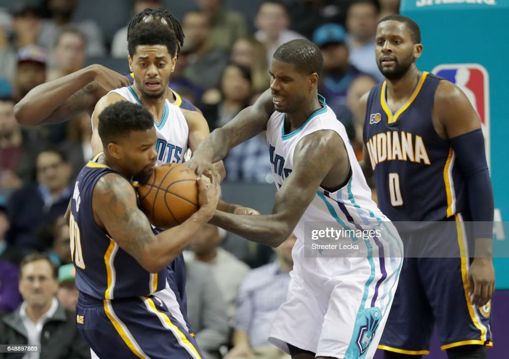 Aaron Brooks #00 of the Indiana Pacers and Marvin Williams #2 of the Charlotte Hornets battle for a loose ball during their game at Spectrum Center on March 6, 2017 in Charlotte, North Carolina.