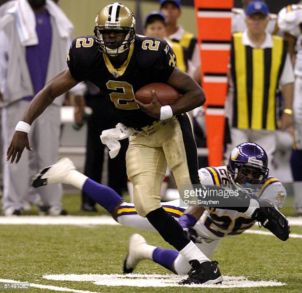 Aaron Brooks of the New Orleans Saints avoids a tackle by Antoine Winfield of the Minnesota Vikings on October 17 2004 at the Superdome in New...
