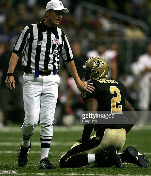 Aaron Brooks of the New Orleans Saints gets a pat on the back from referee Bill Carollo after a penalty against the Atlanta Falcons during the second...