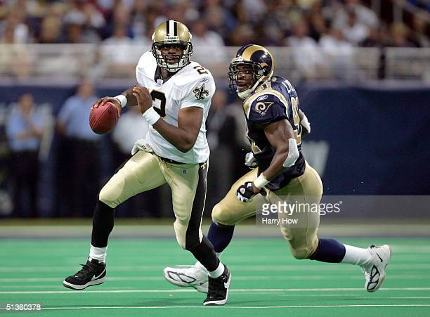 Aaron Brooks of the New Orleans Saints scrambles out of the pocket away from Leonard Little of the St. Louis Rams during the first half at the Edward...
