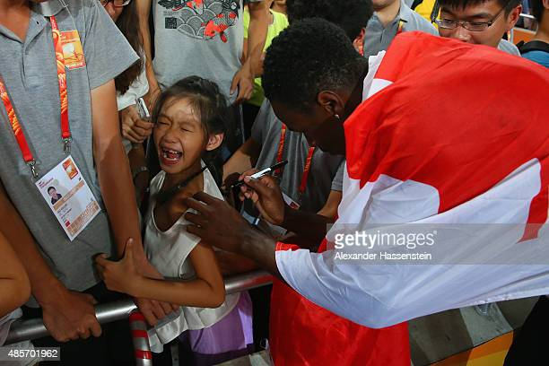 Aaron Brown of Canada signs an autogrpah after his team won bronze in the Men's 4x100 Metres Relay final during day eight of the 15th IAAF World...