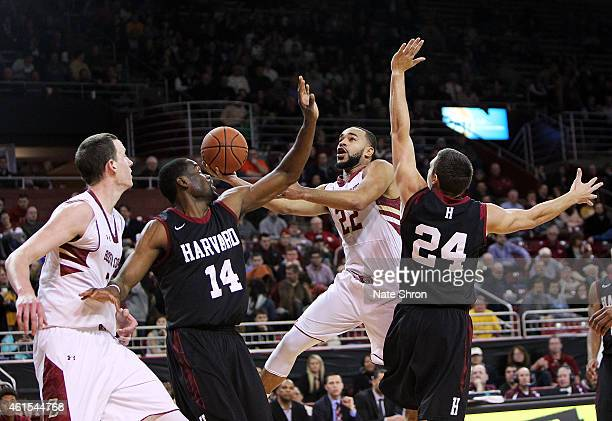 Aaron Brown of the Boston College Eagles puts the ball up to the basket against Steve Moundou-Missi and Jonah Travis of the Harvard Crimson during...