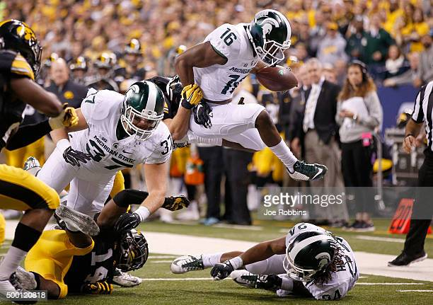 Aaron Burbridge of the Michigan State Spartans leaps with the ball against the Iowa Hawkeyes in the Big Ten Championship at Lucas Oil Stadium on...