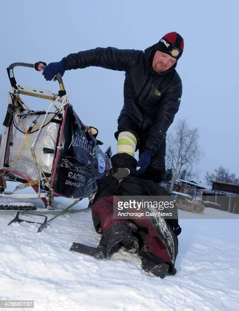 Aaron Burmeister winces with pain as he takes off his bibs at the Nikolai checkpoint during the 2014 Iditarod Trail Sled Dog Race on Tuesday March 4...