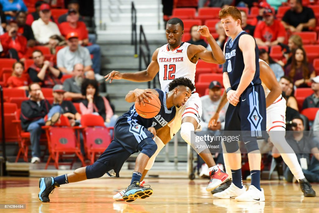 Aaron Calixte #1 of the Maine Black Bears drives to the basket against Keenan Evans #12 of the Texas Tech Red Raiders during the first half of the game on November 14, 2017 at United Supermarkets Arena in Lubbock, Texas.