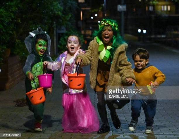 Aaron Cana, Noa and Ezdra pose for a picture as they go trick-or-treating for Halloween in east London on October 31, 2020.
