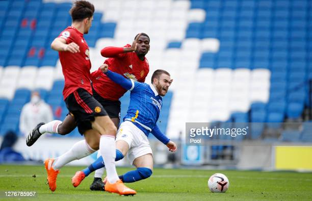 Aaron Connolly of Brighton and Hove Albion is brought down inside the penalty area by Paul Pogba of Manchester United, leading to a VAR review that...