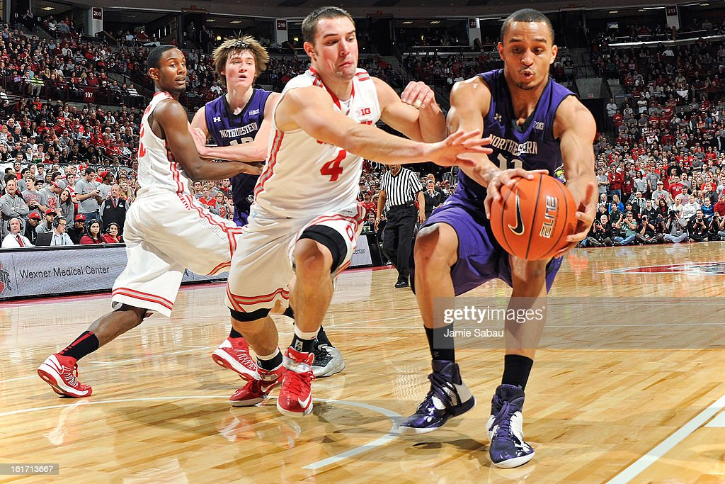 Aaron Craft #4 of the Ohio State Buckeyes and Reggie Hearn #11 of the Northwestern Wildcats chase down a loose ball in the first half on February 14, 2013 at Value City Arena in Columbus, Ohio.