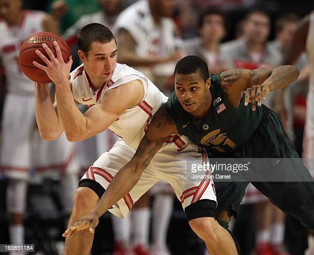 Aaron Craft of the Ohio State Buckeyes controls the ball against Keith Appling of the Michigan State Spartans during a semifinal game of the Big Ten...