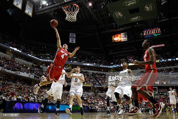 Aaron Craft of the Ohio State Buckeyes drives for a shot attempt against Zack Novak of the Michigan Wolverines during their Semifinal game of the...