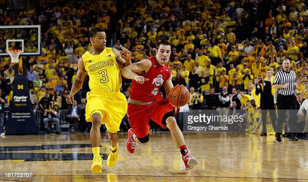Aaron Craft of the Ohio State Buckeyes drives past Trey Burke of the Michigan Wolverines at Crisler Center on February 5 2013 in Ann Arbor Michigan...