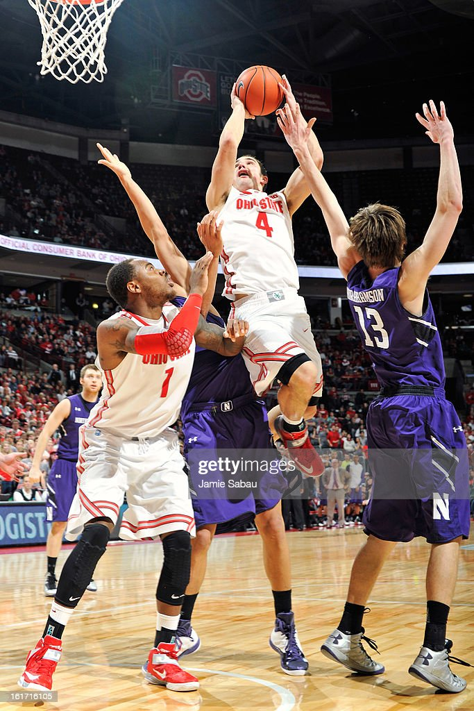 Aaron Craft #4 of the Ohio State Buckeyes drives to the basket in the second half against Kale Abrahamson #13 of the Northwestern Wildcats as Deshaun Thomas #1 of the Buckeyes watches on February 14, 2013 at Value City Arena in Columbus, Ohio. Ohio State defeated Northwestern 69-59.