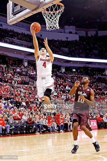 Aaron Craft of the Ohio State Buckeyes gets past Amos Olatayo of the LouisianaMonroe Warhawks to score a basket during the first half at Value City...