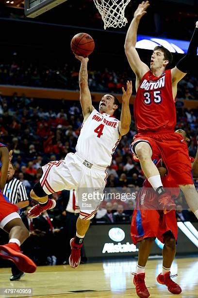 Aaron Craft of the Ohio State Buckeyes goes up for a shot as Matt Kavanaugh of the Dayton Flyers defends during the second round of the 2014 NCAA...