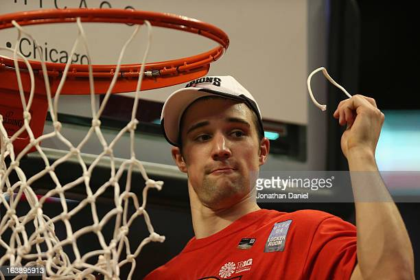 Aaron Craft of the Ohio State Buckeyes takes a piece of the net after the Buckeyes defeated the Wisconsin Badgers during the Big Ten Basketball...