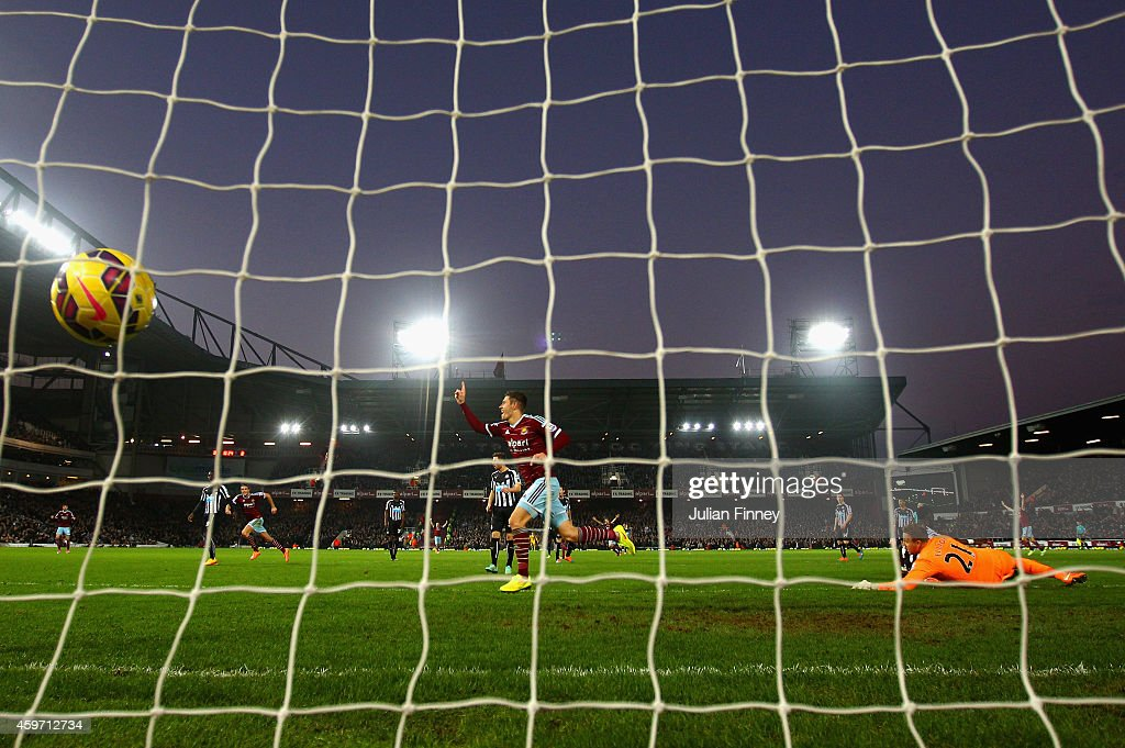 Aaron Cresswell of West Ham celebrates scoring opening goal past Robert Elliot of Newcastle United during the Barclays Premier League match between West Ham United and Newcastle United at Boleyn Ground on November 29, 2014 in London, England.