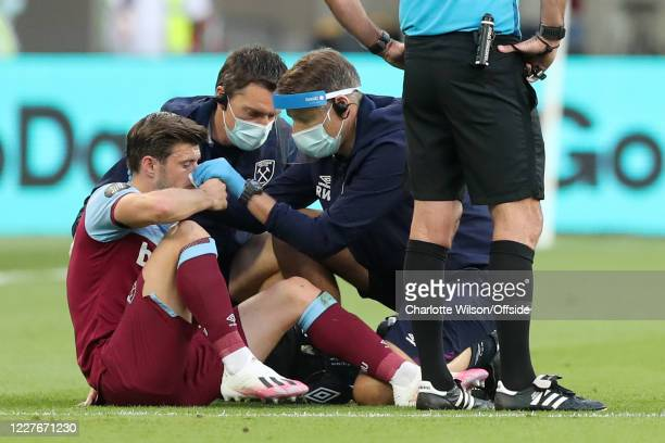 Aaron Cresswell of West Ham is treated for a bloody nose during the Premier League match between West Ham United and Watford FC at London Stadium on...