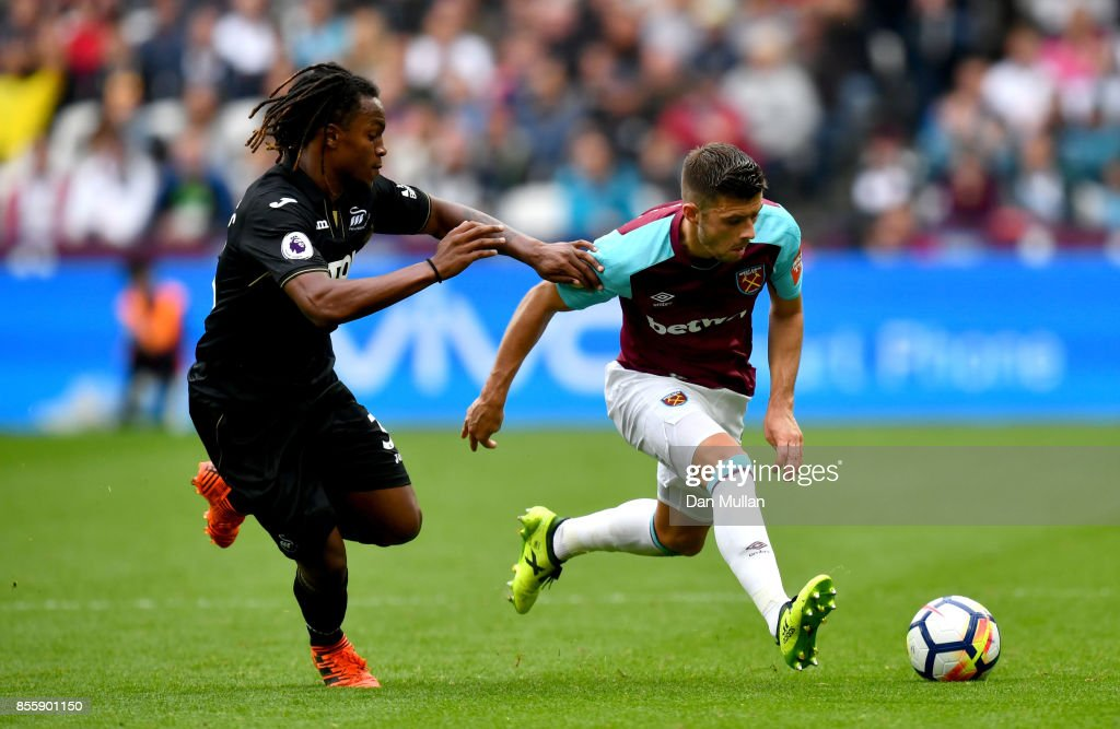 Aaron Cresswell of West Ham United and Renato Sanches of Swansea City compete for the ball during the Premier League match between West Ham United and Swansea City at London Stadium on September 30, 2017 in London, England.