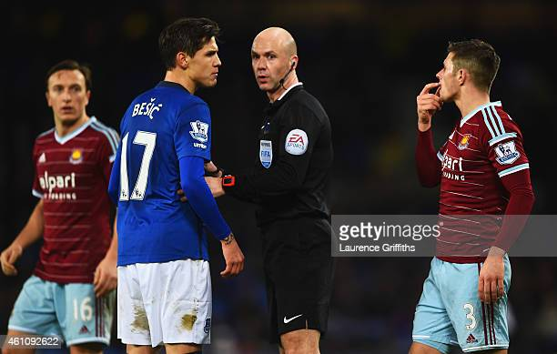Aaron Cresswell of West Ham United argues with Muhamed Besic of Everton as referee Anthony Taylor intervenes during the FA Cup Third Round match...