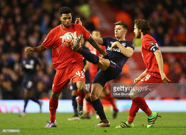 Aaron Cresswell of West Ham United battles with Jerome Sinclair and Joe Allen of Liverpool during the Emirates FA Cup Fourth Round match between...