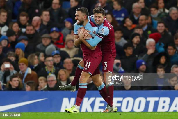 Aaron Cresswell of West Ham United celebrates with teammate Robert Snodgrass after scoring his team's first goal during the Premier League match...