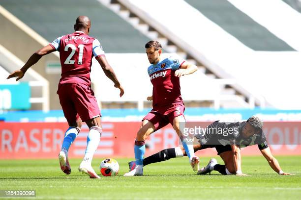 Aaron Cresswell of West Ham United is challenged by Joelinton of Newcastle United during the Premier League match between Newcastle United and West...