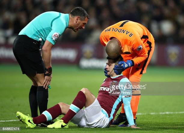 Aaron Cresswell of West Ham United is helped by Darren Randolph of West Ham United after an injury during the Premier League match between West Ham...