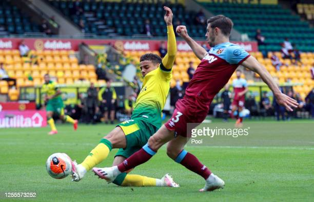 Aaron Cresswell of West Ham United is tackled by Max Aarons of Norwich City during the Premier League match between Norwich City and West Ham United...