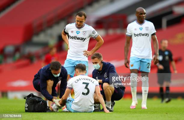 Aaron Cresswell of West Ham United receives medical treatment during the Premier League match between Manchester United and West Ham United at Old...