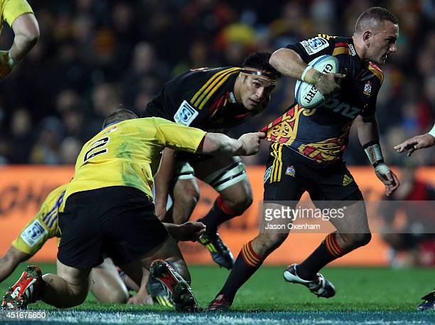 Aaron Cruden of the Chiefs breaks the tackle of Dane Coles of the Hurricanes during the round 18 Super Rugby match between the Chiefs and the...