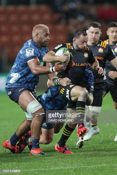 Aaron Cruden of the Chiefs is tackled by Captain Patrick Tuipulotu and James Parsons of the Blues during the Super Rugby match between Waikato Chiefs...