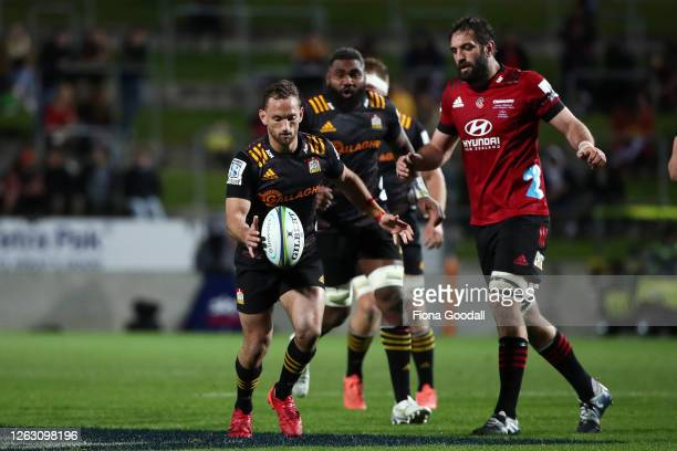 Aaron Cruden of the Chiefs kicks with Sam Whitelock of the Crusaders during the round eight Super Rugby Aotearoa match between the Chiefs and...