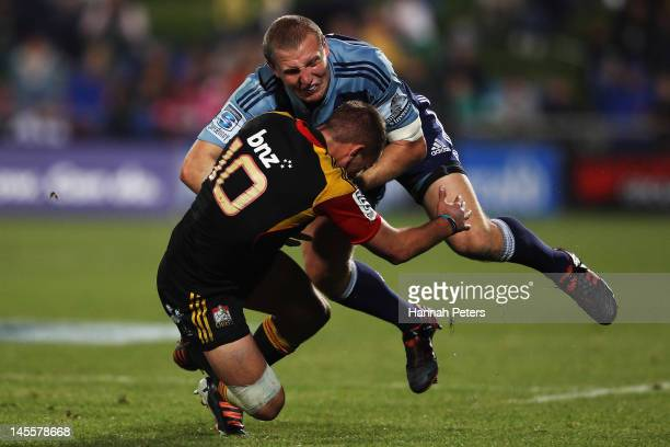 Aaron Cruden of the Chiefs tackles Hadlee Parkes of the Blues during the round 15 Super Rugby match between the Blues and the Chiefs at North Harbour...