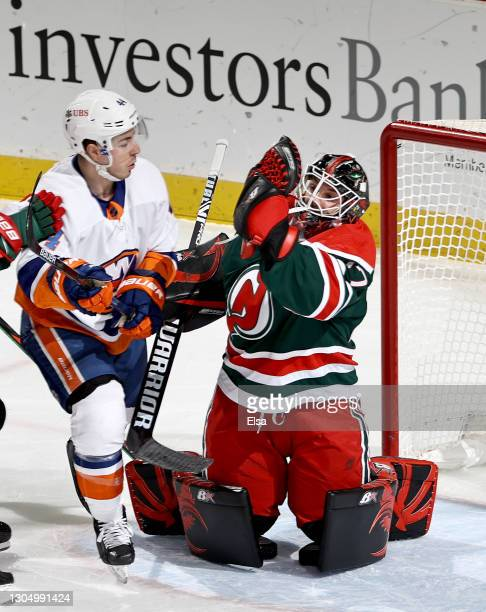 Aaron Dell of the New Jersey Devils makes the save as Jean-Gabriel Pageau of the New York Islanders looks on in the first period at Prudential Center...