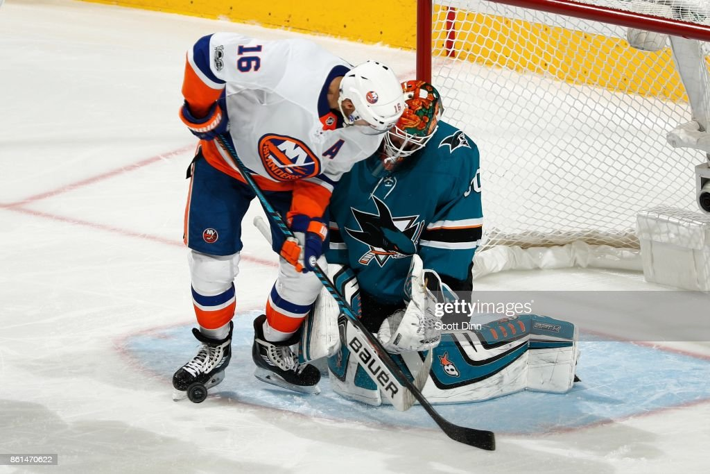 Aaron Dell #30 of the San Jose Sharks makes a save as Andrew Ladd #16 of the New York Islanders looks at SAP Center on October 14, 2017 in San Jose, California.
