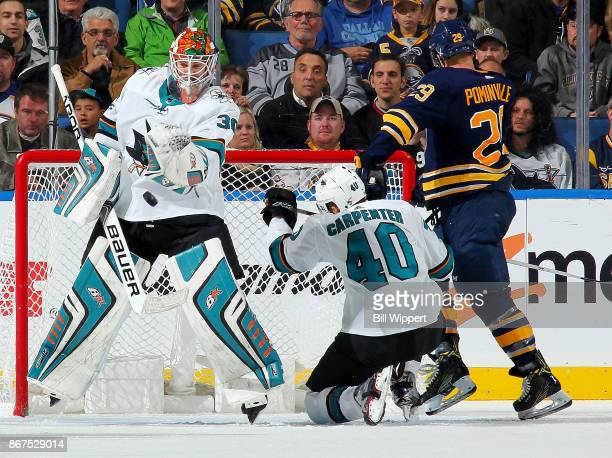 Aaron Dell of the San Jose Sharks makes a save as teammate Ryan Carpenter tangles with Jason Pominville of the Buffalo Sabres alongside the net...