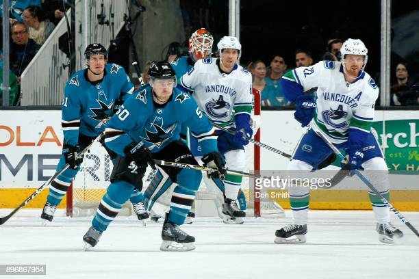 Aaron Dell of the San Jose Sharks protects the net as Justin Braun Chris Tierney of the San Jose Sharks and Markus Granlund and Daniel Sedin of the...