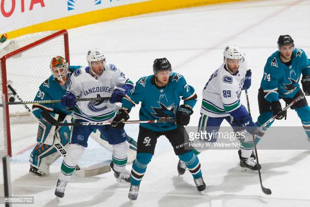 Aaron Dell Tim Heed and Dylan DeMelo of the San Jose Sharks defend against Thomas Vanek and Sam Gagner of the Vancouver Canucks at SAP Center on...