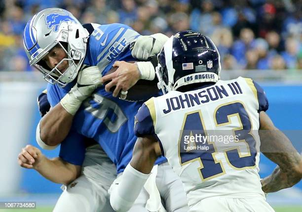 Aaron Donald of the Los Angeles Rams and John Johnson wrap up quarterback Matthew Stafford of the Detroit Lions during the fourth quarter at Ford...