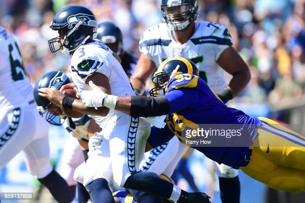 Aaron Donald of the Los Angeles Rams dives to get to Russell Wilson of the Seattle Seahawks during the game at Los Angeles Memorial Coliseum on...