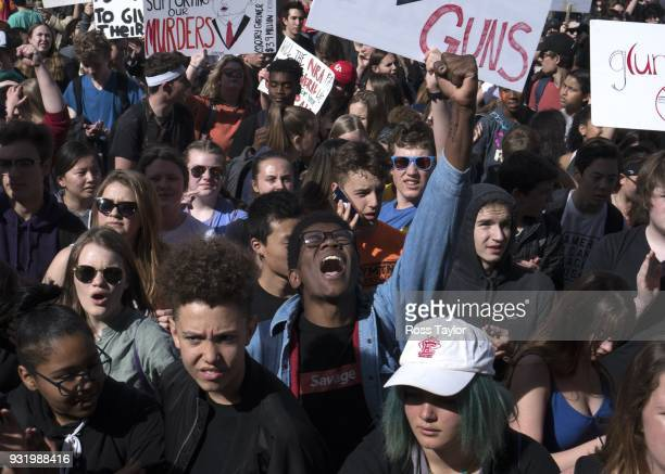 Aaron Durst a student at East High School in Denver raises his hand in protest against gun violence on the Colorado State Capitol grounds on March 14...