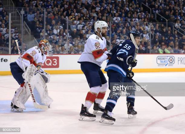 Aaron Ekblad of the Florida Panthers and Mark Scheifele of the Winnipeg Jets set a screen in front of goaltender James Reimer as they keep an eye on...