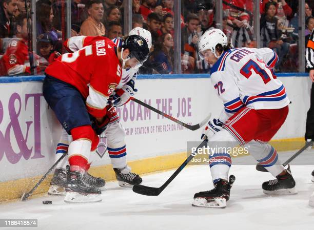 Aaron Ekblad of the Florida Panthers battles for control of the puck with Artemi Panarin #10 and Filip Chytil of the New York Rangers at the BBT...