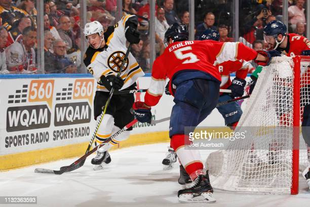 Aaron Ekblad of the Florida Panthers defends against Noel Acciari of the Boston Bruins as he circles behind the net with the puck at the BBT Center...