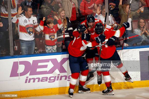 Aaron Ekblad of the Florida Panthers is swarmed by teammates after scoring in overtime for the win against the Anaheim Ducks at the BBT Center on...