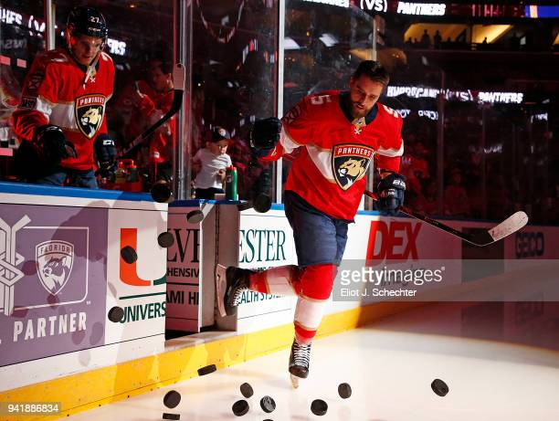 Aaron Ekblad of the Florida Panthers knocks practice pucks out onto the ice for warm ups prior to the start of the game against the Carolina...