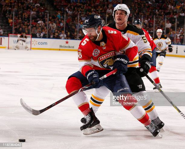 Aaron Ekblad of the Florida Panthers skates for possession against Noel Acciari of the Boston Bruins at the BBT Center on March 23 2019 in Sunrise...