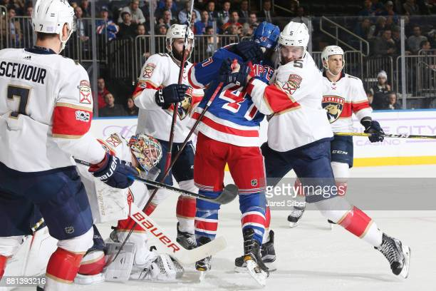 Aaron Ekblad of the Florida Panthers ties up Steven Kampfer of the New York Rangers near the net at Madison Square Garden on November 28 2017 in New...
