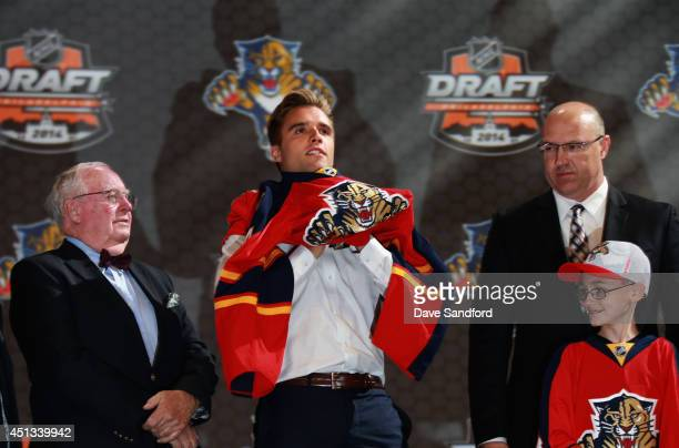 Aaron Ekblad puts on his jersey after being selected first overall by the Florida Panthers during the 2014 NHL Entry Draft at Wells Fargo Center on...
