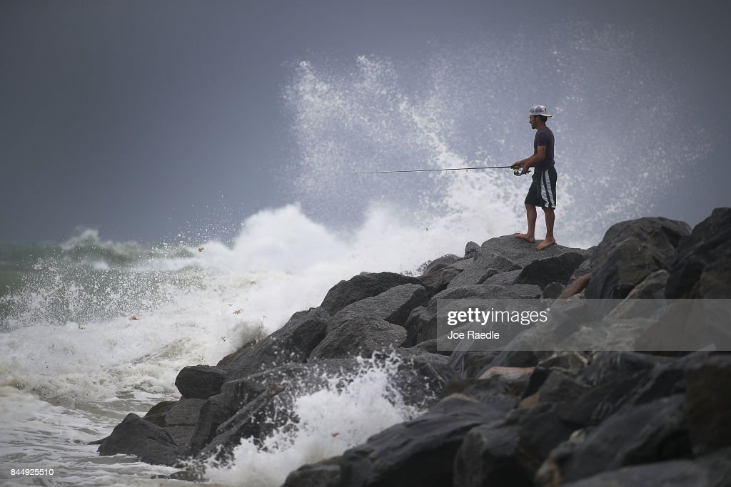 Aaron Elbaz fishes in the churning ocean as Hurricane Irma approaches on September 9, 2017 in Miami Beach, Florida. Florida is in the path of the Hurricane which may come ashore at category 4.